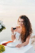 smiling curly woman holding wineglass on romantic date on seashore