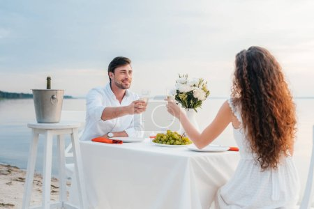 boyfriend and girlfriend clinking with champagne glasses during romantic date on seashore