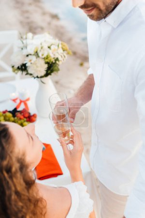 cropped view of couple clinking with champagne glasses during romantic date on seashore