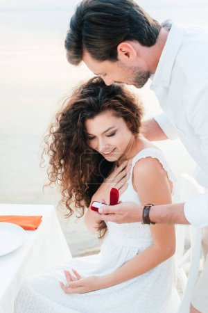 man making propose with ring to girlfriend in romantic date