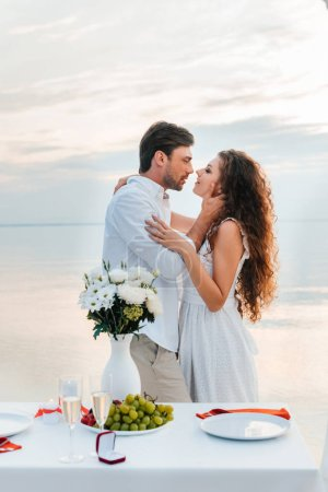 happy couple hugging and kissing near table with proposal ring