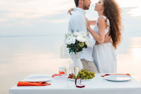 selective focus on couple hugging near table with proposal ring