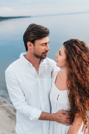 young romantic couple looking at each other and embracing on beach