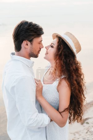 happy couple looking at each other and embracing on seashore