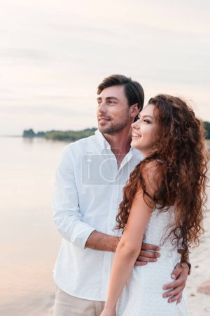 beautiful romantic couple hugging on seashore