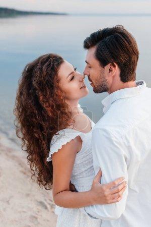 Photo pour Heureux couple romantique regardant les uns les autres et faire place au bord de mer - image libre de droit