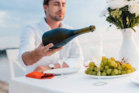 selective focus of man pouring champagne into glass on romantic date