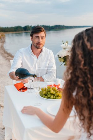 man pouring champagne for girlfriend during romantic date on beach