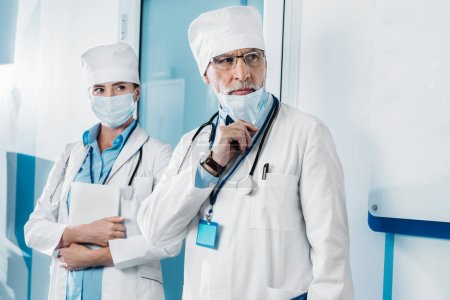 Photo for Serious male doctor taking off medical mask while his colleague standing behind with digital tablet in hospital corridor - Royalty Free Image