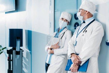Photo pour Médecins masculins et féminins en masques à usage médical permanent avec le presse-papiers et tablette numérique dans le couloir de l'hôpital - image libre de droit