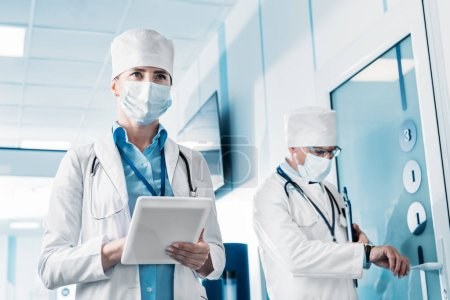 low angle view of female doctor in medical mask using digital tablet while her male colleague standing behind with clipboard in hospital corridor