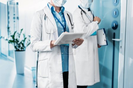Photo for Partial view of female doctor in medical mask using digital tablet while her male colleague standing behind with clipboard in hospital corridor - Royalty Free Image