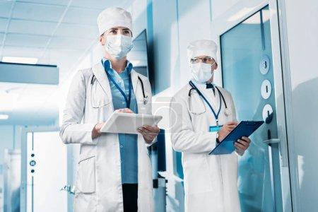 Foto de Vista de ángulo bajo de doctora en máscara médica con la tableta digital mientras que su colega masculino parado detrás con portapapeles en pasillo de hospital - Imagen libre de derechos