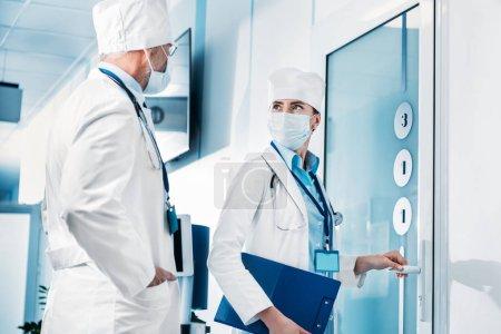 Photo pour Femme médecin avec presse-papiers, ouverture de porte et de parler à un collègue masculin dans le couloir de l'hôpital - image libre de droit