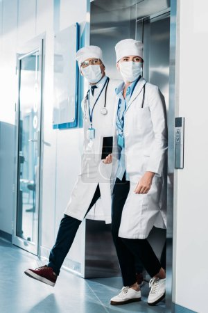 Photo for Male and female doctors with digital tablet and clipboard walking out from elevator in hospital corridor - Royalty Free Image