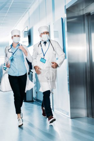 male and female doctors with digital tablet and clipboard running in hospital corridor