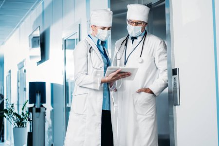 Photo for Selective focus of female doctor in medical mask showing digital tablet to male colleague in hospital corridor - Royalty Free Image