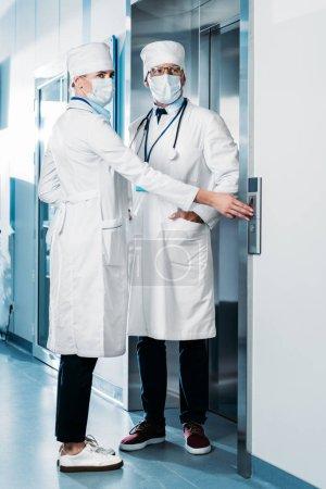 Photo pour Médecins masculins et féminins des masques d'examens médicaux en poussant le bouton de l'ascenseur dans le couloir de l'hôpital - image libre de droit