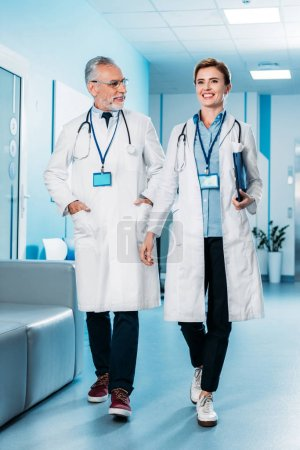 smiling female and male doctors with badges and stethoscopes over neck walking in hospital corridor