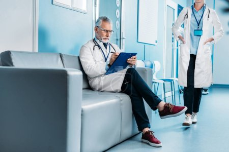 pensive middle aged male doctor writing in clipboard and sitting on sofa while his female colleague walking behind in hospital corridor