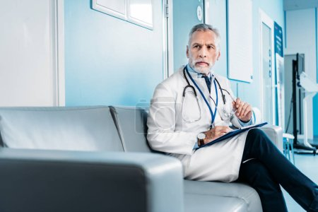 middle aged male doctor with clipboard looking away and sitting on couch in hospital corridor