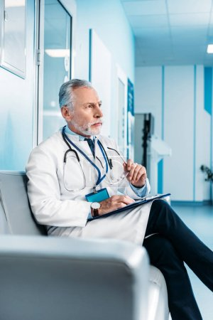 focused mature male doctor with clipboard holding sitting on couch in hospital corridor