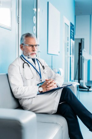 pensive middle aged male doctor with clipboard sitting on couch in hospital corridor