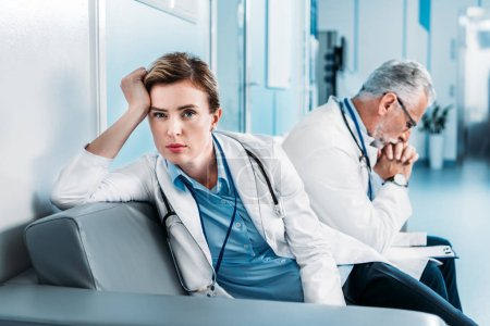 tired female doctor looking at camera on sofa while her male colleague sitting behind in hospital corridor