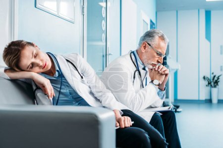 female doctor sleeping on couch while her male colleague sitting behind in hospital corridor