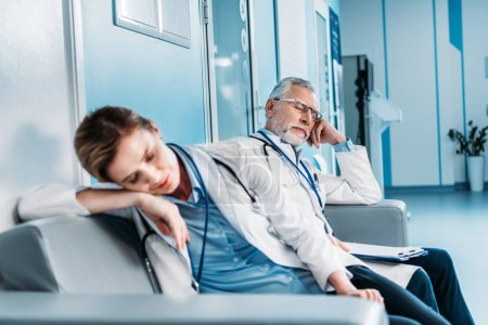 exhausted male and female doctors sleeping on sofa in hospital corridor