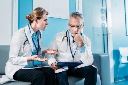 Photo pour Adulte femme médecin émotionnel gestuelle par des mains et avoir discuté avec une collègue masculin sur le canapé dans le couloir de l'hôpital - image libre de droit