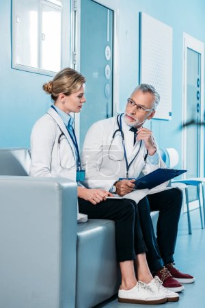 male and female doctors talking on couch in hospital corridor