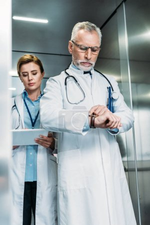 Photo pour Confiance moyen âgé homme médecin vérification montre-bracelet tandis que son collègue à l'aide de tablette numérique derrière dans l'ascenseur de l'hôpital - image libre de droit