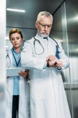 confident middle aged male doctor checking wristwatch while his female colleague using digital tablet behind in hospital elevator