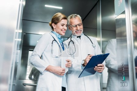happy mature male doctor showing clipboard to female colleague with digital tablet in hospital elevator