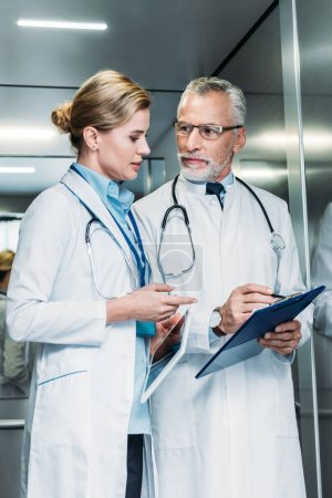 male doctor showing clipboard to female colleague with digital tablet in hospital elevator