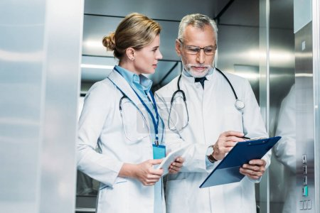 mature male doctor showing clipboard to female colleague with digital tablet in hospital elevator