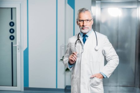 middle aged male doctor with stethoscope over neck looking at camera in hospital