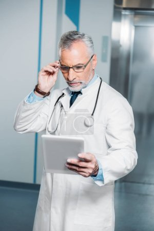 mature male doctor with stethoscope over neck adjusting eyeglasses and looking at digital tablet in hospital