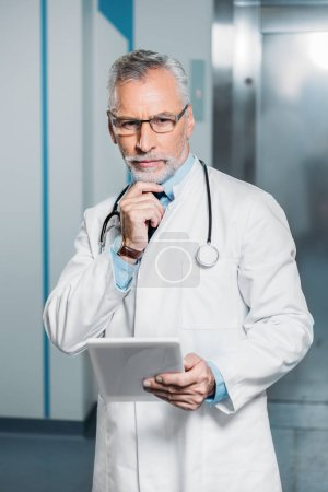 serious mature male doctor with stethoscope over neck looking at camera and holding digital tablet in hospital