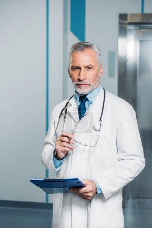 middle aged male doctor with stethoscope over neck holding eyeglasses with clipboard and looking at camera in hospital