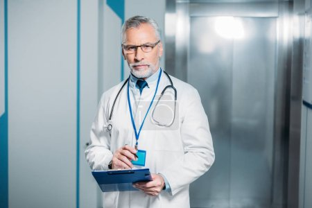 confident mature male doctor with stethoscope over neck holding clipboard and looking at camera in hospital