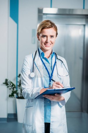 Photo for Happy female doctor with stethoscope over neck writing in clipboard and looking at camera in hospital - Royalty Free Image