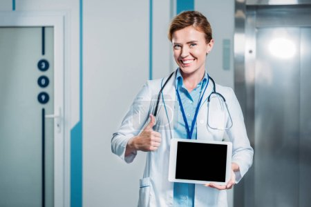 Photo for Happy female doctor with stethoscope over neck showing digital tablet with blank screen and doing thumb up gesture in hospital - Royalty Free Image