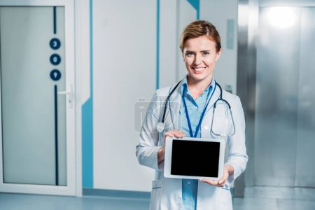 smiling female doctor with stethoscope over neck showing digital tablet with blank screen in hospital