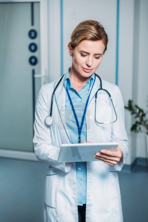 adult female doctor with stethoscope over neck using digital tablet in hospital
