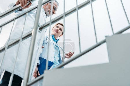 low angle view of male and female doctors talking and walking on staircase in hospital
