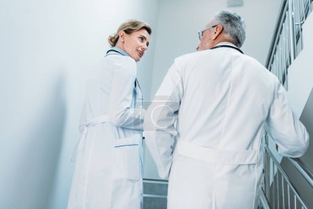 Photo for Rear view of male and female doctors talking and walking on staircase in hospital - Royalty Free Image