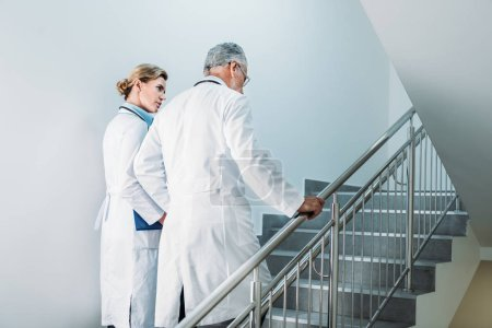rear view of male and female doctors walking on staircase in hospital