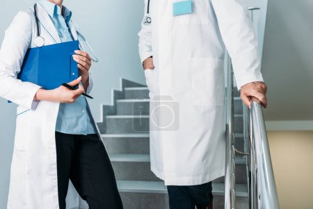 cropped image of male and female doctors with stethoscopes standing on staircase in hospital